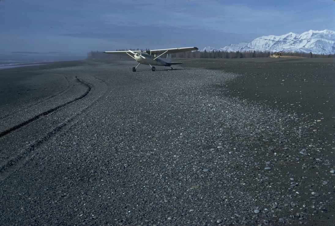 Photo: Small plane parked on mixed-substrate beach.