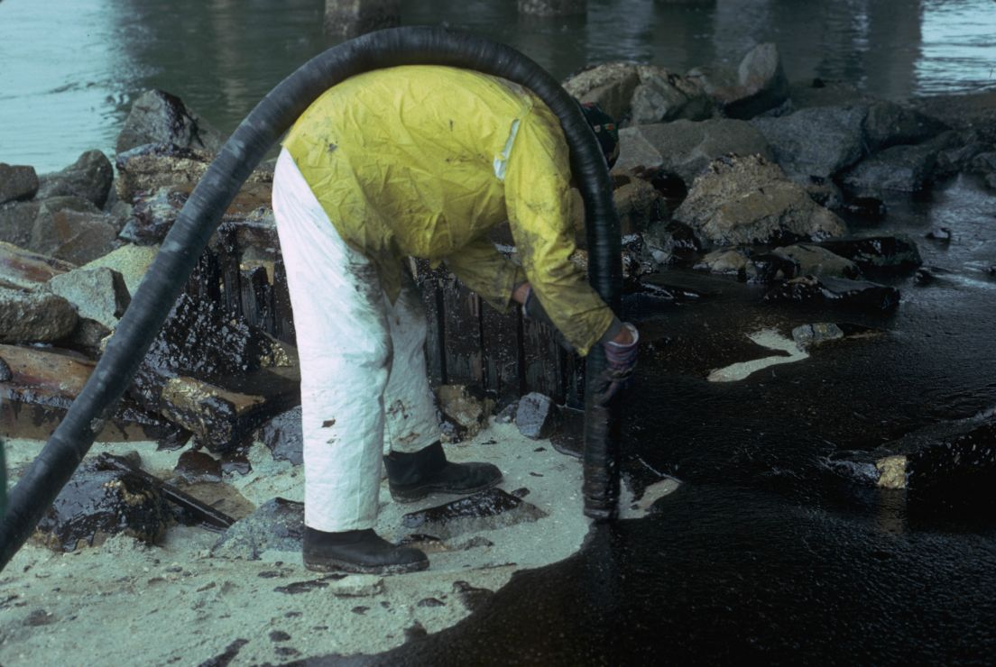 Photo of worker with vacuum hose sucking up oil off of sand.
