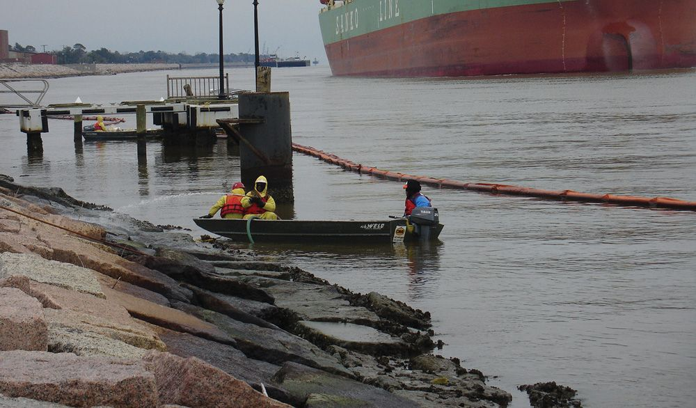 Workers clean oil from rocks following spill.