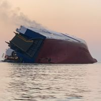 Smoke rises from a large freighter vessel on its side.