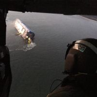A person in a helicopter looking down at a large freighter vessel on its side.