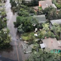 An aerial image of a flooded residential area with oil sheens visible in the water.