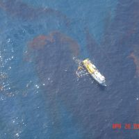 An aerial view of a skimming vessel moving through a patch of oil.