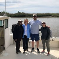 A group of four people on a boat posing for a photo.