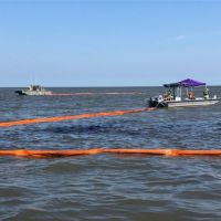 Several vessels drag a skimming boom across the water's surface where a patch of oil is visible.