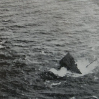 A black and white photo of a sinking vessel.