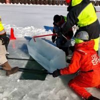 Three people lifting a block of ice from the surface.