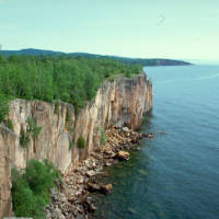 A rocky cliff side with water below.