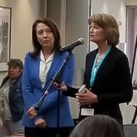 Two women standing at a microphone.
