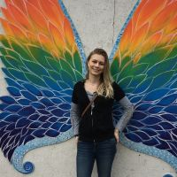 A person posing with rainbow butterfly wings.