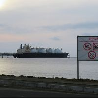 Large vessel on the water, sign in foreground.