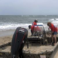 Three people working to dislodge a derelict vessel from the sand on a beach.