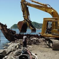Large construction equipment tearing apart a derelict vessel.