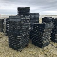 Stacks of bins on a beach.