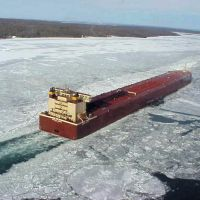 A vessel moving through ice on a river.