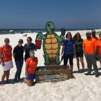 People pose on a beach with a large cut out sign of a turtle.