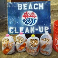 Milk jugs holding collected cigarette butts next to a beach cleanup sign.