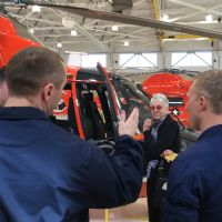 Two men listen as woman speaks next to a helicopter.