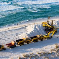 Heavy equipment removing sand from a beach.