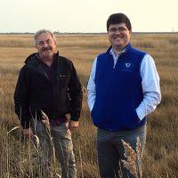 Two men standing in a field.