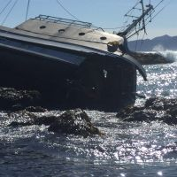 Grounded vessel on its side on a beach.