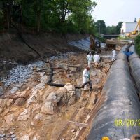 Workers in a streambed, next to two large pipes.