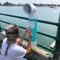 """Woman installing a """"bin"""" on a pier."""