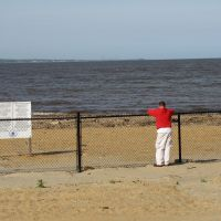 Beach with a fence, sign, and person looking out at water.