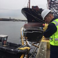 Workers on boats attempt to contain oil spilled into the water.