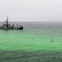 Long-Range Autonomous Underwater Vehicle surfacing in a plume of bright green dye near a vessel in the water.