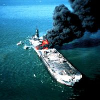 Large vessel in flames on the water.