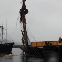 Removal of part of a sunken vessel and derelict nets from water.