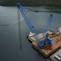 Aerial photo of vessel surrounded by boom with heavy equipment on a dock.