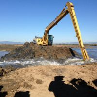 Heavy equipment digging at a levee.