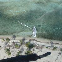 Aerial view of a sailboat aground near a beach.