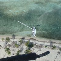 Sailboat on its side in shallow water near the beach.