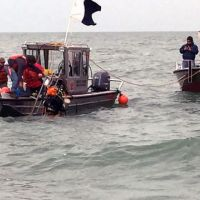 Divers exit small boats into the waters of Lake Erie.