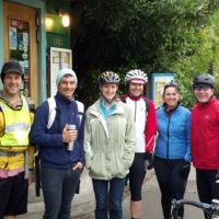 Six people wearing bike helmets standing next to bikes.
