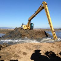 Excavator removing earth to allow tide waters into the recovering wetland.