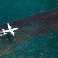 A plane releases chemical dispersant to break up an oil slick