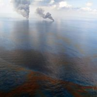 Oil on the ocean and smoke visible in the distance.