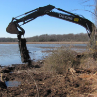 Excavator removes metal debris from the shore of a coastal landfill.