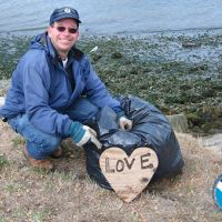 Man near the ocean with trash bag pointing to wooden heart enscribed with love.