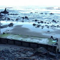 The steel, concrete, and foam Japanese dock beached at Olympic National Park.