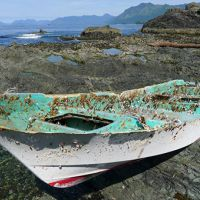 Small boat on rocky shoreline.