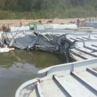 A view of damaged barge with boom and sorbent pads in the water.