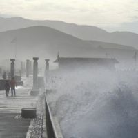 Large waves break on a pier that people are walking along.