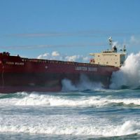 Large waves crash on a huge cargo ship aground on a beach.