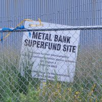 Sign behind a fence reading Metal Bank Super Fund Site.
