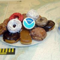 A mug, ruler & NOAA chart with a stack of donuts, one decorated with NOAA logo